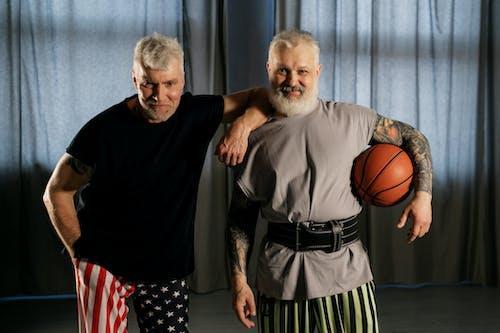 Elderly Men Smiling while Holding a Basketball