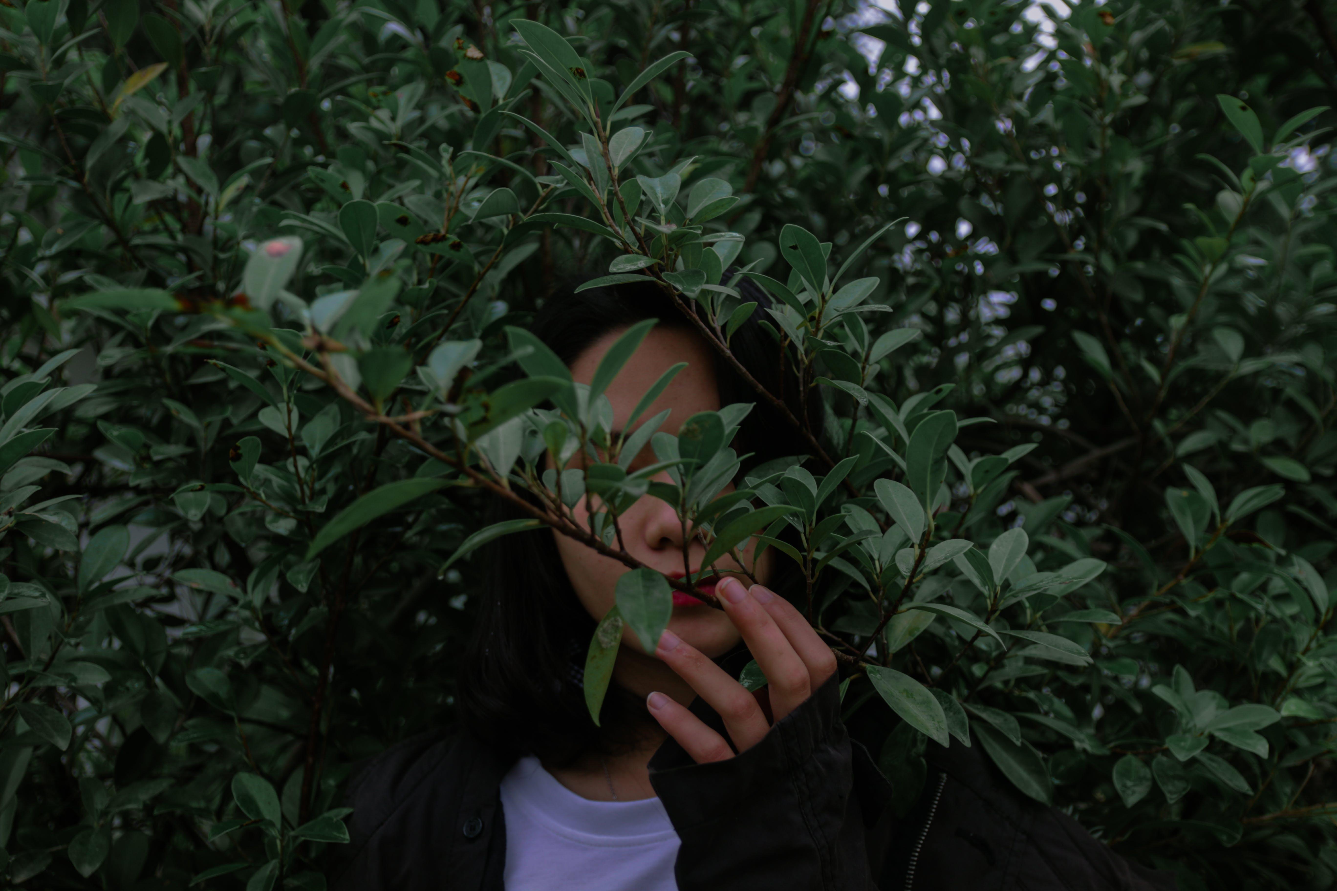 Woman Wearing Black Jacket Beside Green Leaved Trees