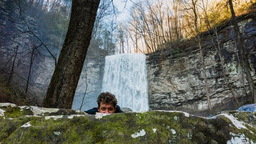 Young male hiker hiding behind boulder near waterfall in forest