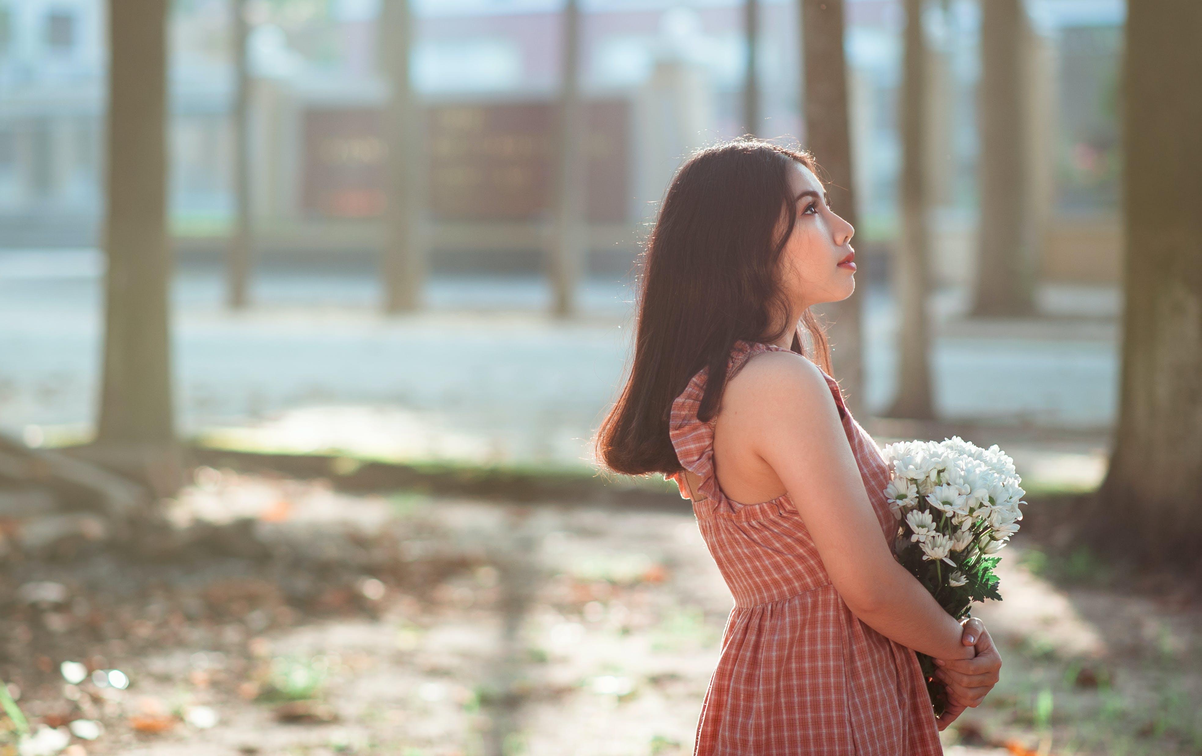 Woman Wearing Brown Sleeveless Dress Carrying White Flower Bouquet