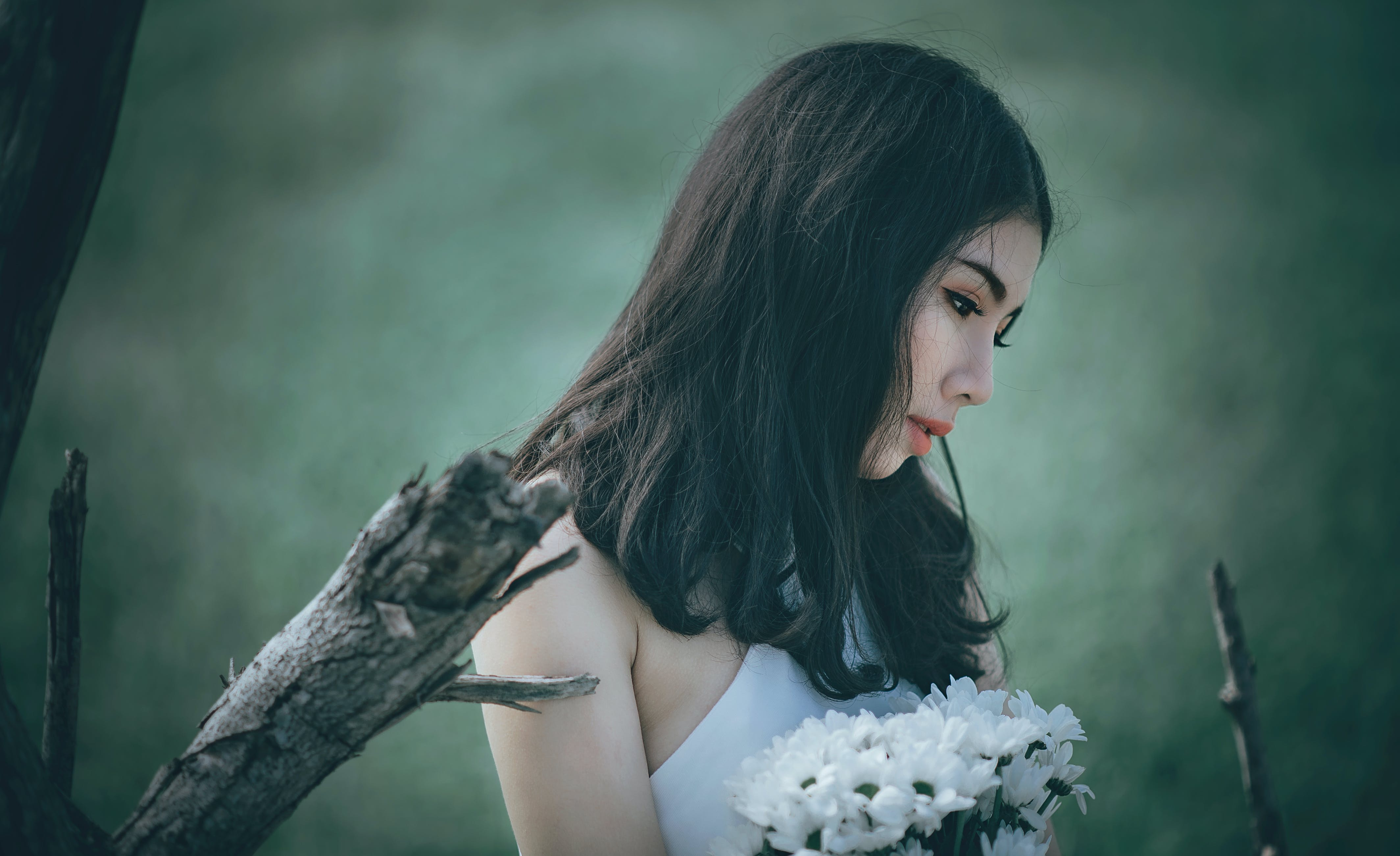 Woman in White Top Holding Bouquet of White Petaled Flowers While Looking Down