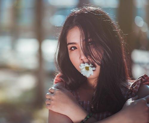 Gratis stockfoto met aantrekkelijk mooi, Aziatisch meisje, bijten, bloem