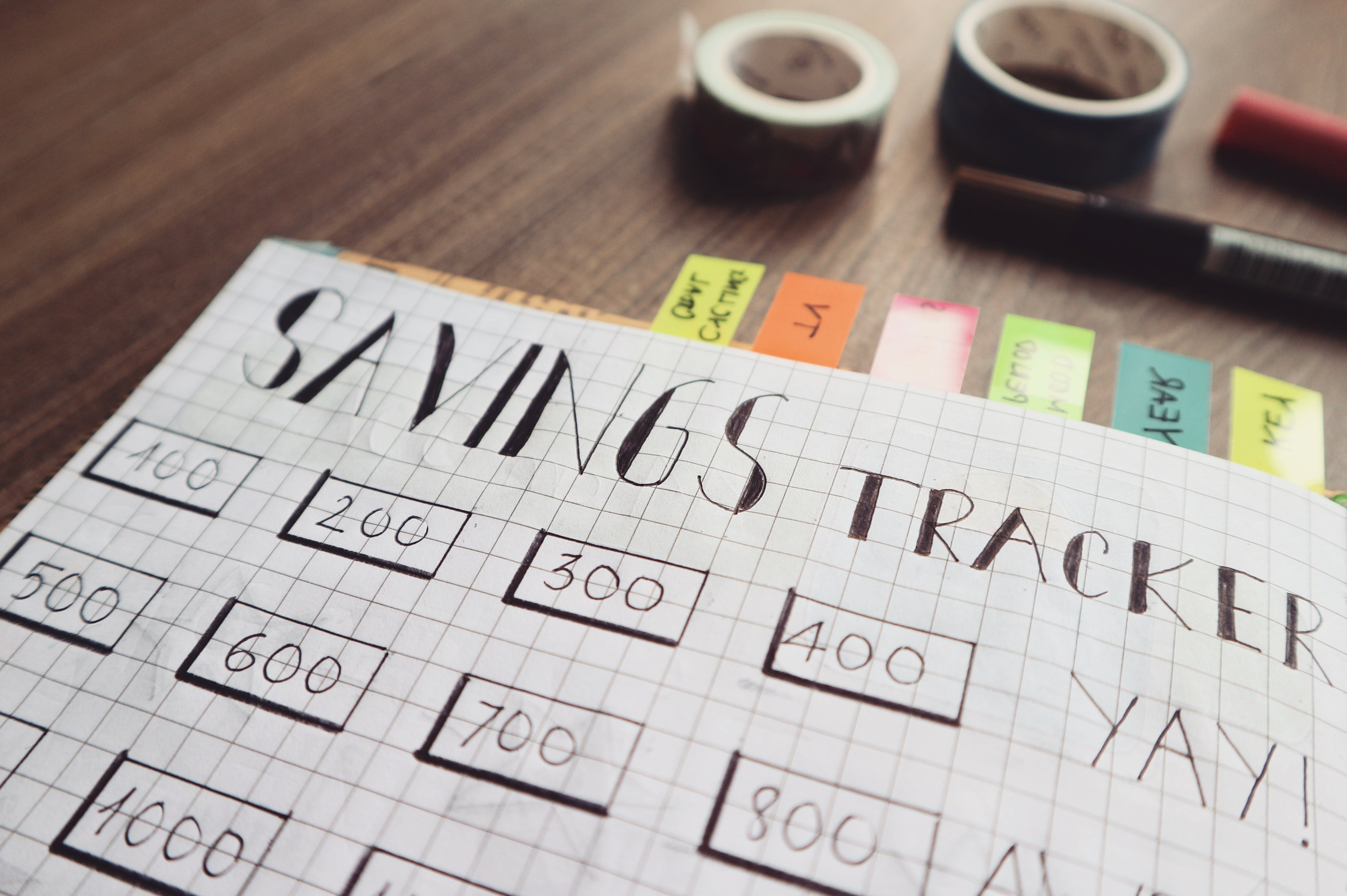 Savings Tracker on Brown Wooden Surface