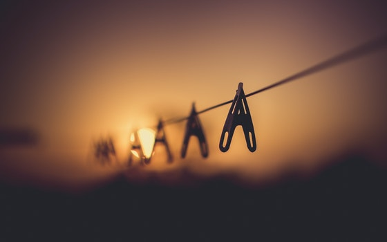 Shallow Focus Photography of Wooden Clothes Clip on Clothes String Rack