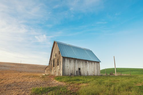 Photo of Beige and Gray Wooden Barn House on Green Grass