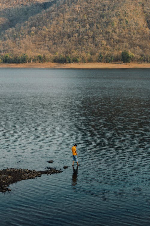 Person in Yellow Jacket and Black Pants Standing on Brown Rock Near Body of Water during