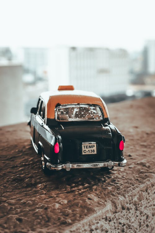 Back view of retro car cab toy placed on uneven concrete surface on blurred city background