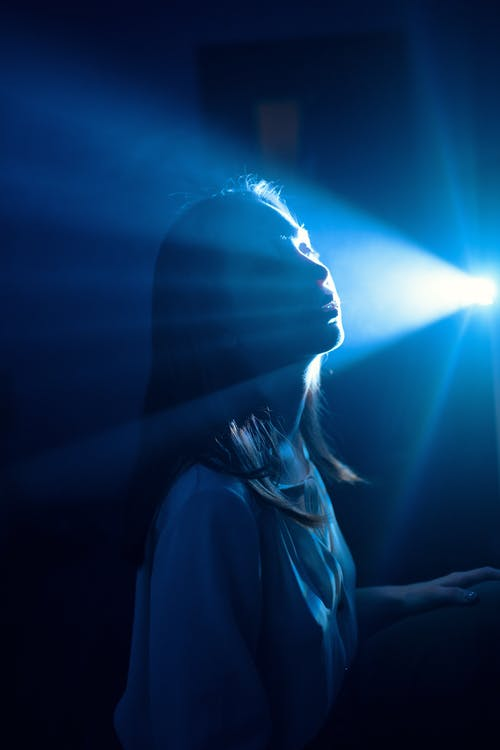 Side view of young mindful female in blouse against bright light beam in back lit