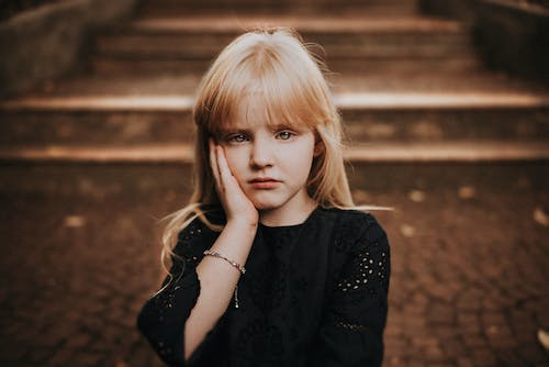 Sad little girl touching face and looking at camera in autumn park