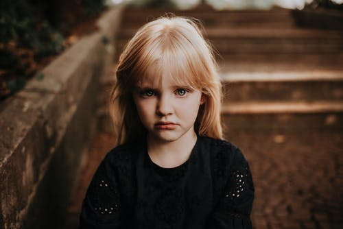 Serious little girl with long blond hair looking at camera sadly while standing near steps in autumn park