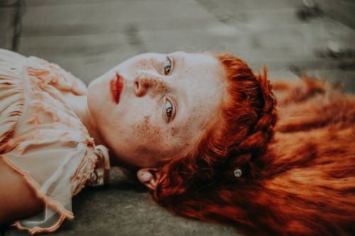 Contemplative redhead girl lying on ground and looking at camera with calmness