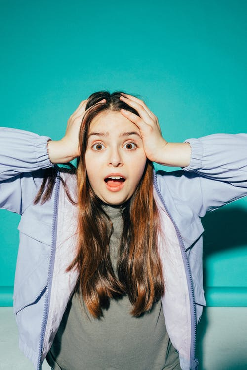Shocked Girl With her Hands on her Head