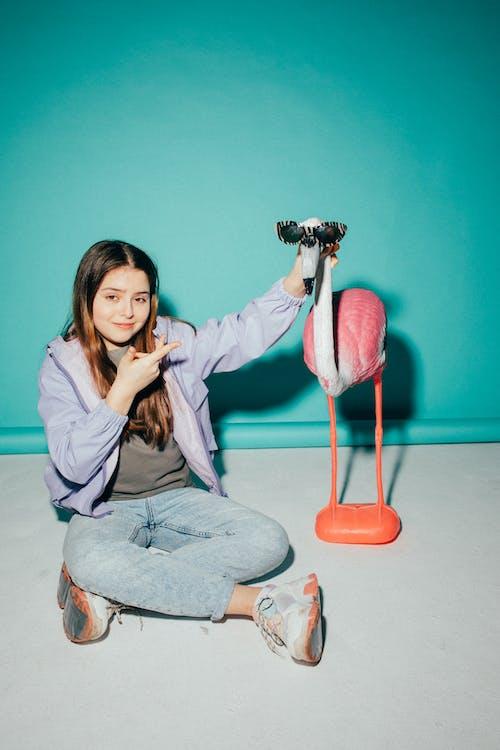 Girl Posing Beside a Flamingo Figurine