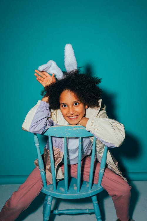 Girl Wearing a Jacket Sitting on a Chair