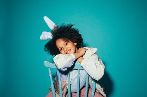 Girl Wearing Bunny Ears Sitting on a Wooden Chair