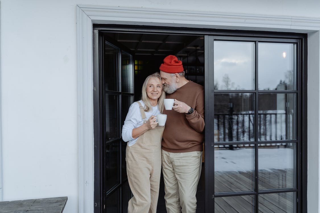 Man and Woman Standing by the Door Holding Mugs