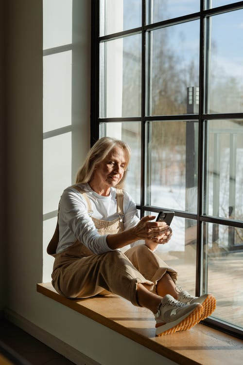 Woman in White Long Sleeve Shirt Sitting by the Window