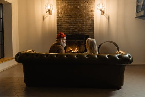People Sitting on a Couch In Front of a Fireplace