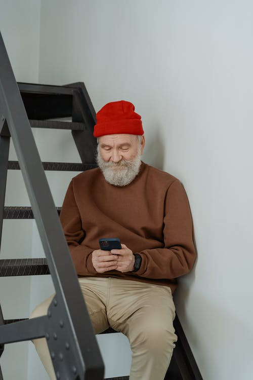 Man Wearing a Brown Sweater Using a Smartphone