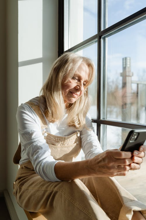 Woman in White Long Sleeve Shirt Holding a Black Smartphone