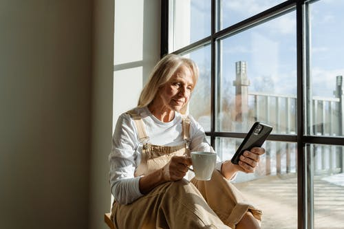 Woman in White Long Sleeve Shirt Holding a Smartphone