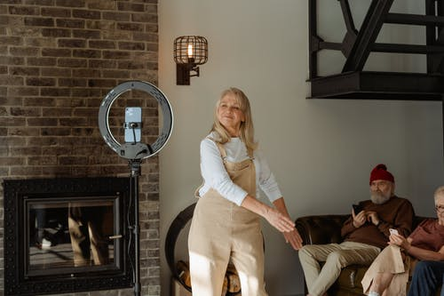 Woman in White Long Sleeve Shirt Standing by the Fireplace