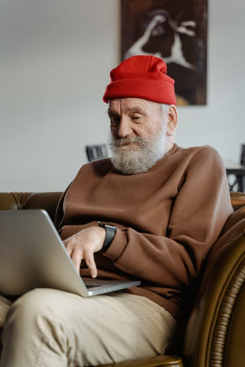 Man in Brown Sweater Using a Laptop