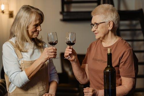 Women Holding Wine Glasses