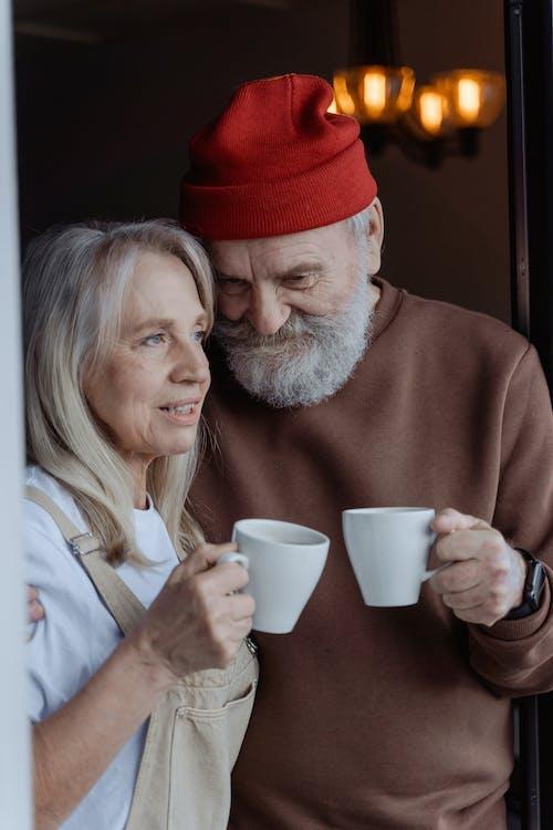 Man in Red Knit Cap Holding White Ceramic Mug
