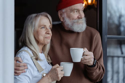 Man and Woman Holding White Ceramic Mugs