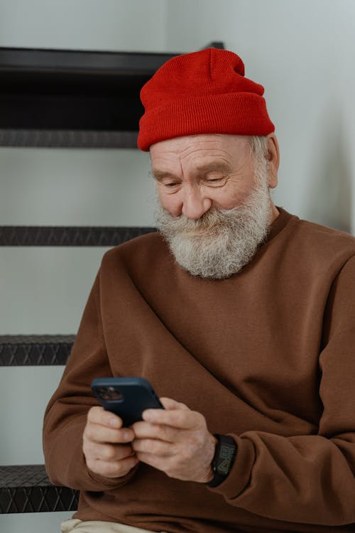 Man in Brown Sweater Holding a Smartphone