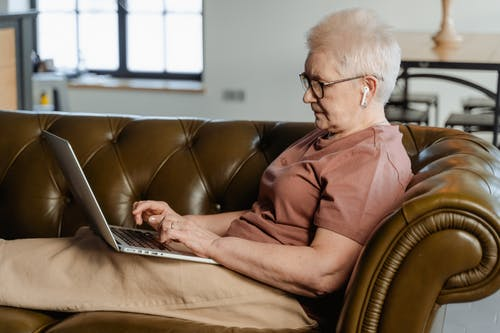 Woman in Brown Shirt Using a Laptop