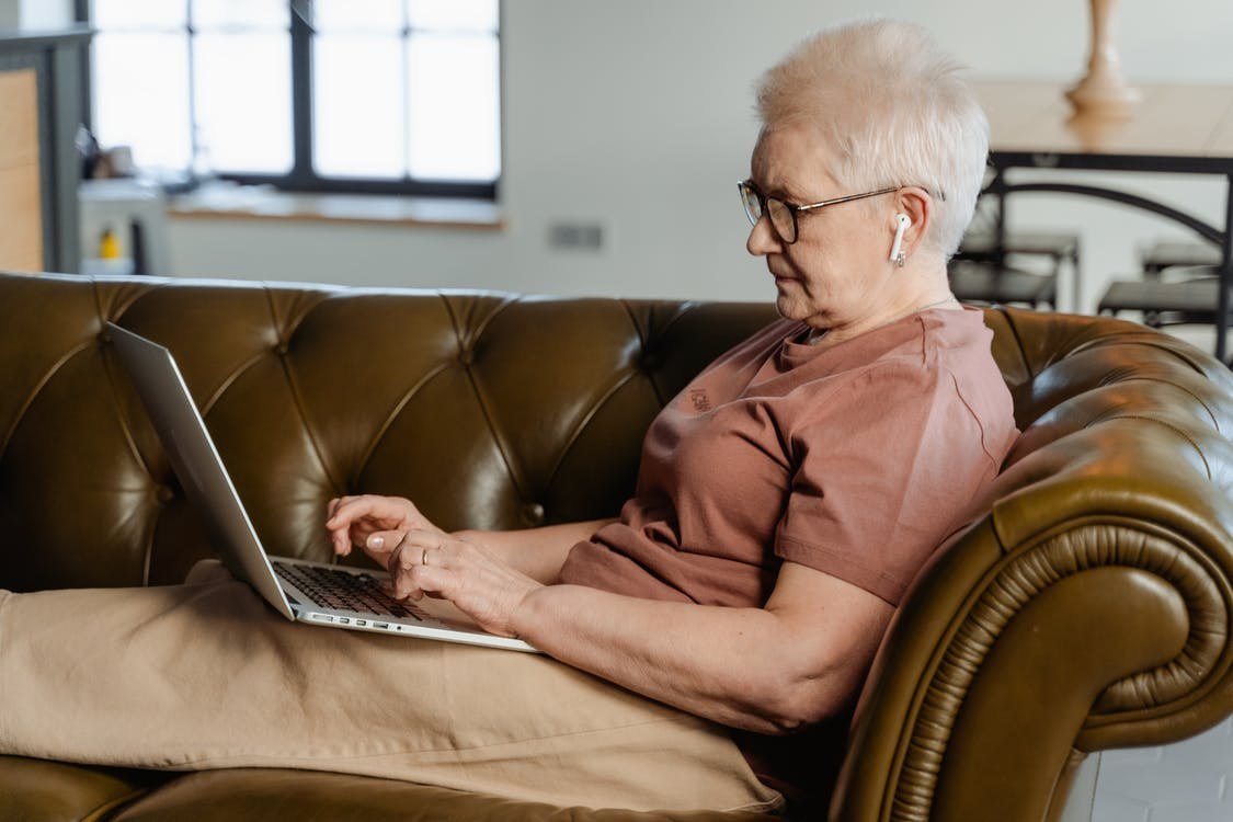 Woman in Brown Dress Shirt Using Macbook Pro
