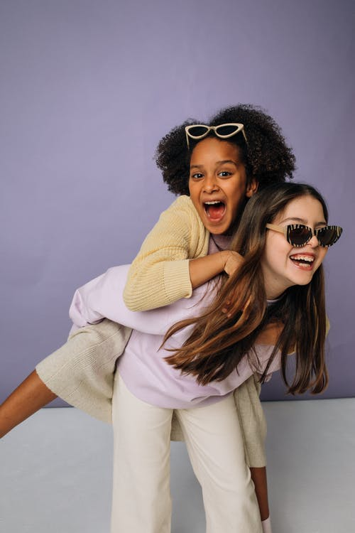Girl Wearing a Sweater Giving her Friend a Piggy Back Ride
