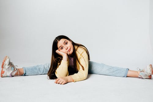Girl in Sweater and Jeans Sitting on White Floor