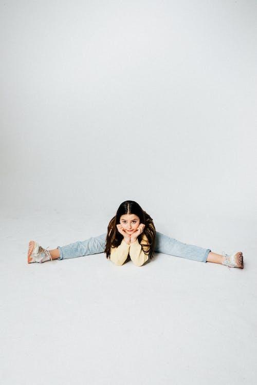 Girl in Blue Denim Jeans Sitting on White Floor