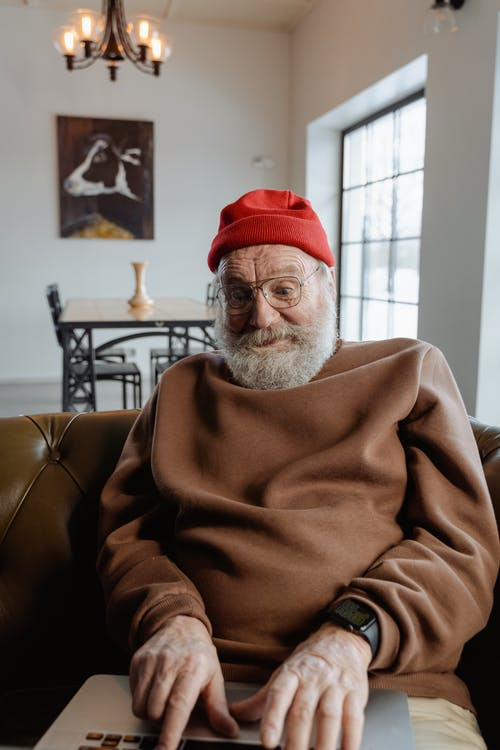 Man in Brown Sweater and Red Knit Cap Sitting on Brown Leather Sofa