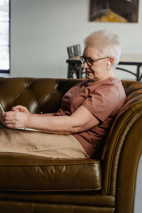 Woman in Brown Shirt Sitting on Brown Leather Couch
