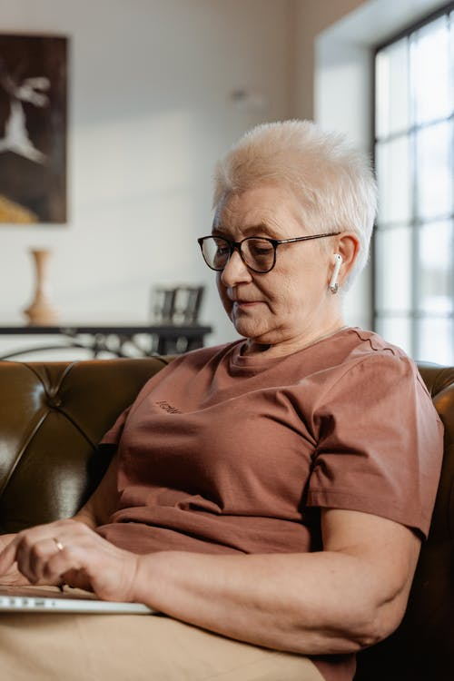 Woman Wearing a Brown Shirt Sitting on a Couch