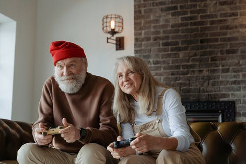 Man in Red Knit Cap and Woman in White Long Sleeve Shirt Sitting on a Leather Couch