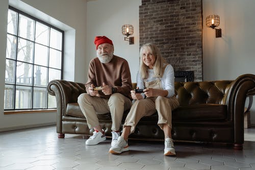 Man and Woman Sitting on Brown Leather Couch