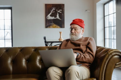 Man in Brown Sweater and Red Beanie Sitting on Brown Leather Couch