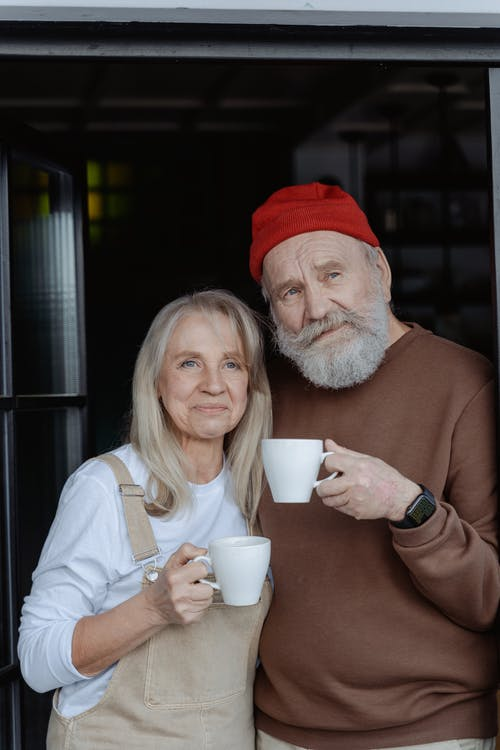 Man in Brown Sweater Holding White Ceramic Mug Beside Woman in White Long Sleeve Shirt