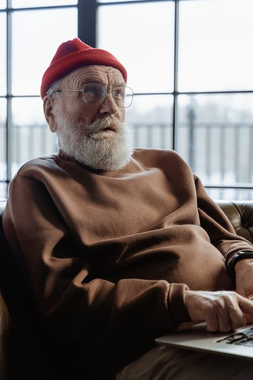 Man in Brown Sweater Wearing Red Beanie Sitting on Chair