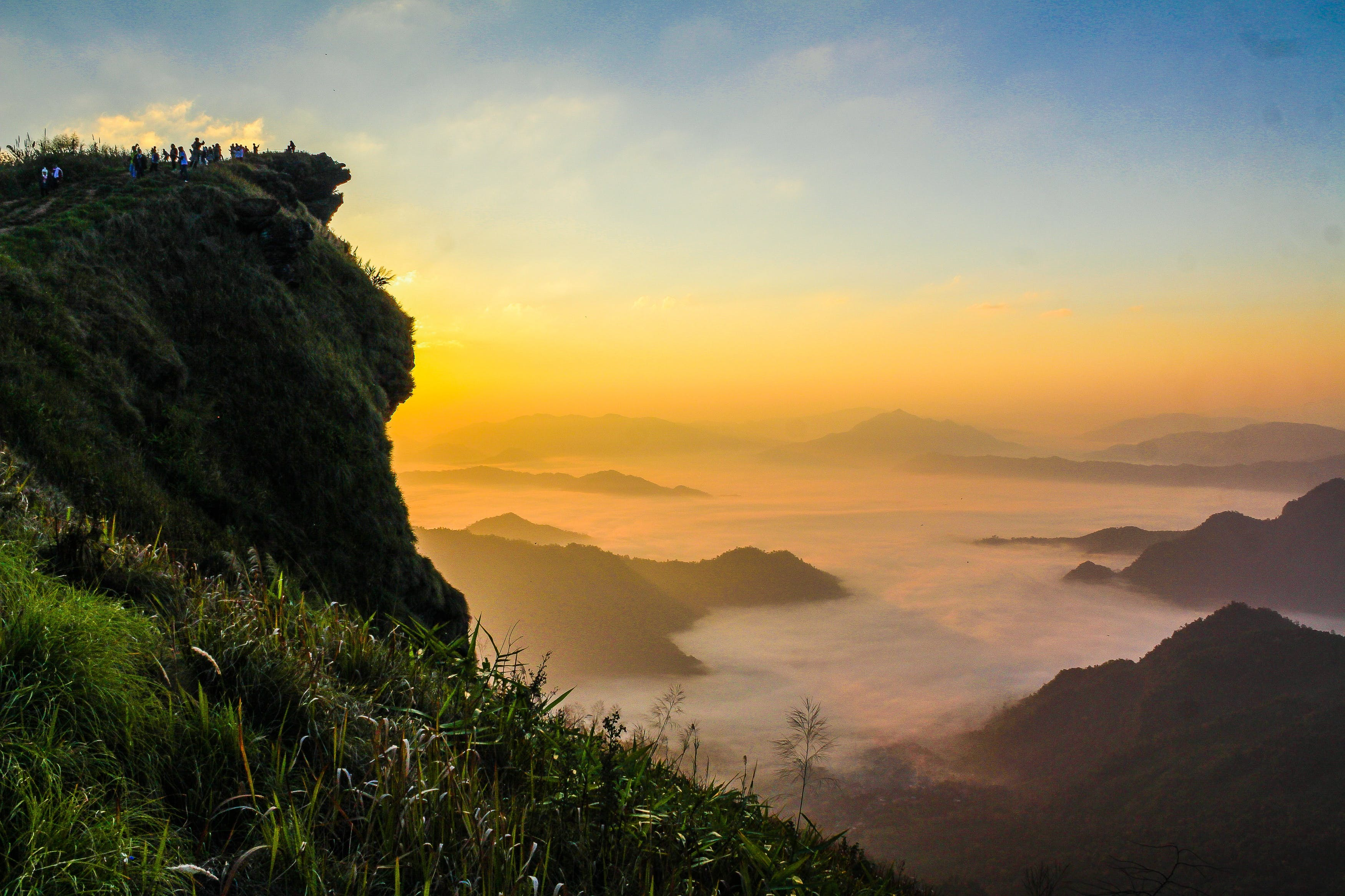 Landscape Photography of Cliff With Sea of Clouds during Golden Hour
