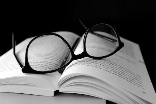 Black Framed Wayfarer Eyeglasses on Book