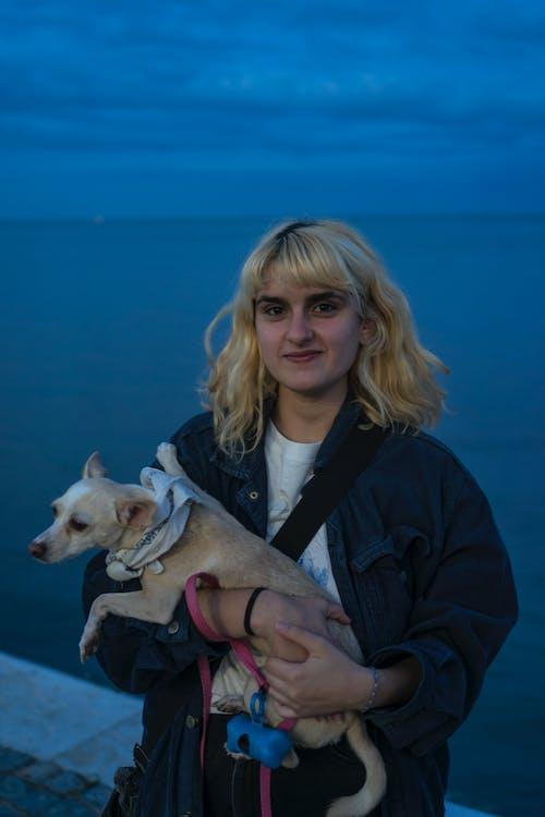 Woman in Black Jacket Holding White Short Coated Small Dog