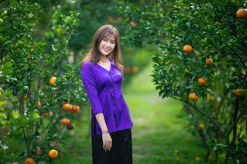 Cheerful Asian female in stylish clothes standing among mandarin trees in garden and looking away in daytime