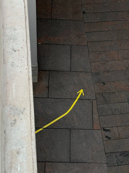 Yellow Plastic Hose on Brown Brick Floor