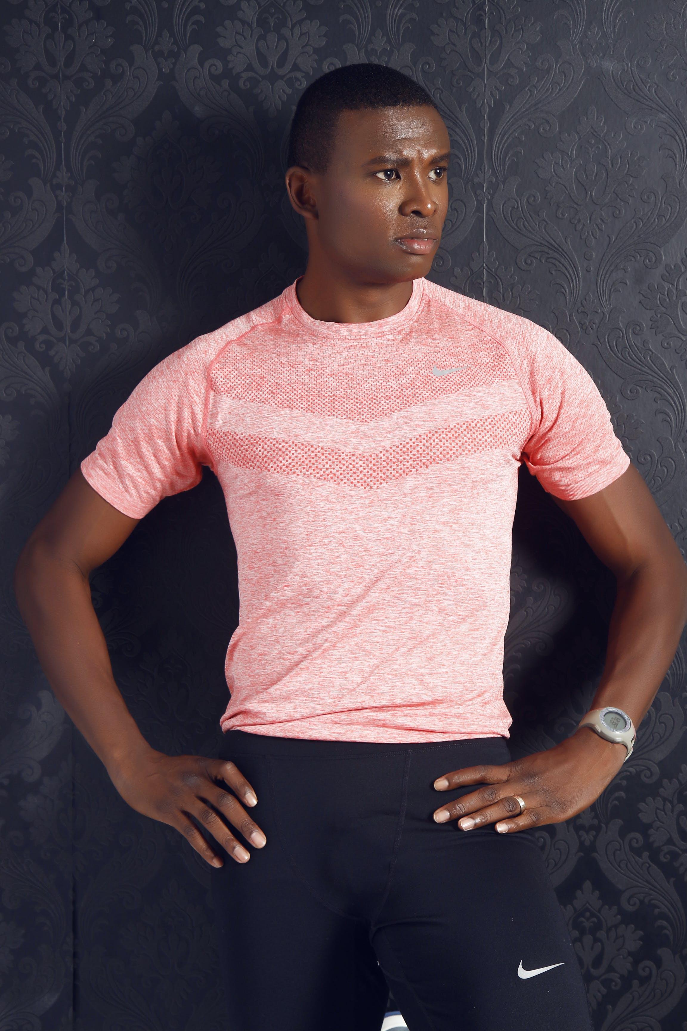 Man Wearing Pink Crewneck Shirt and Black Nike Shorts Standing